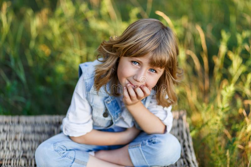 A portrait of a cute little boy with blue eyes and long blond hair sitting on a basket outside at sunset royalty free stock photo