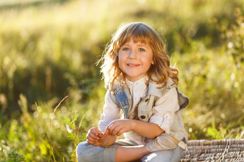 A portrait of a cute little boy with blue eyes and long blond hair sitting on a basket outside at sunset stock image