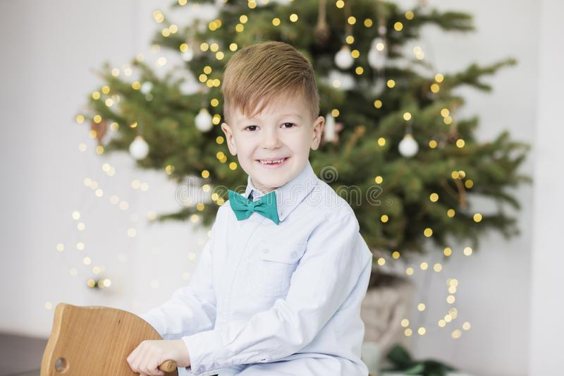 Portrait of a cute little boy. Little boy among Christmas decorations. Boy riding a rocking deer. Rocking deer chair for kids stock images