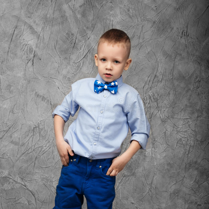 Portrait of a cute little boy in jeans, blue shirt and bow tie o royalty free stock images