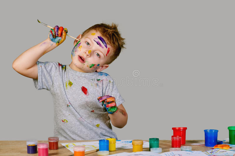 Portrait of a cute little boy messily playing with paints stock image