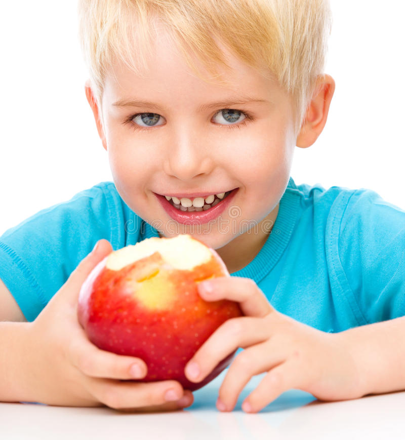 Portrait of a cute little boy with red apple. Isolated over white stock image