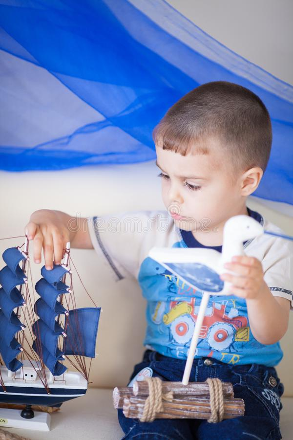 Portrait of cute little boy with ship in his hands. Little sailor plays in his room. Nautical concept stock images