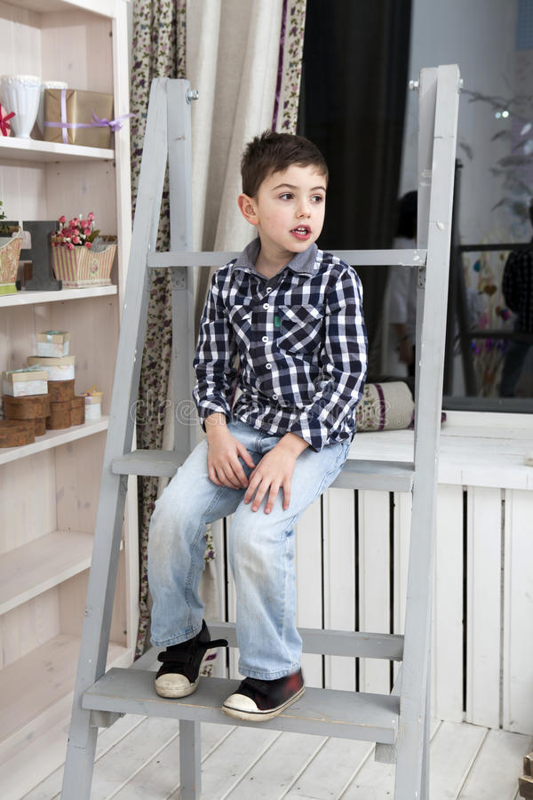 Portrait of a cute little boy sitting on the staircase. Near commode royalty free stock photos