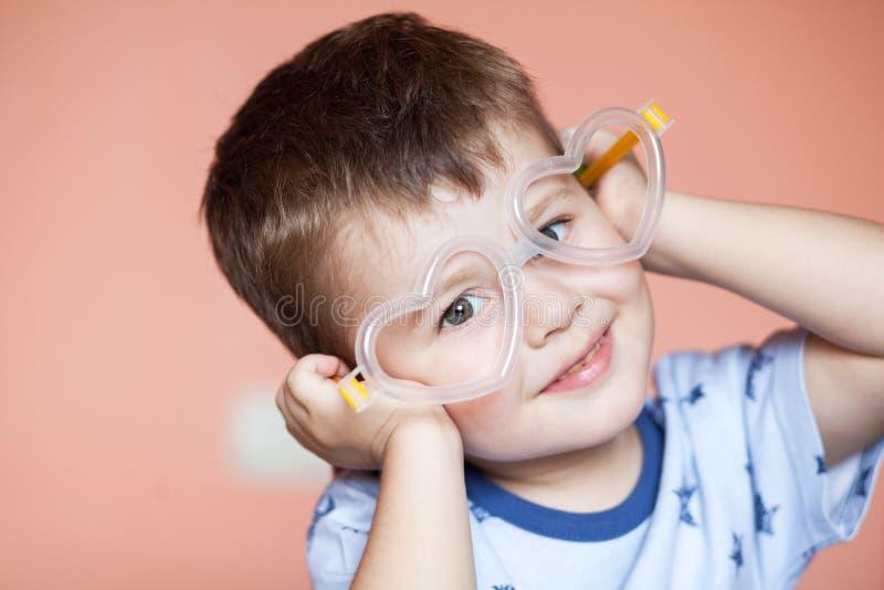 Portrait of cute little boy wearing heart shaped glasses stock photo