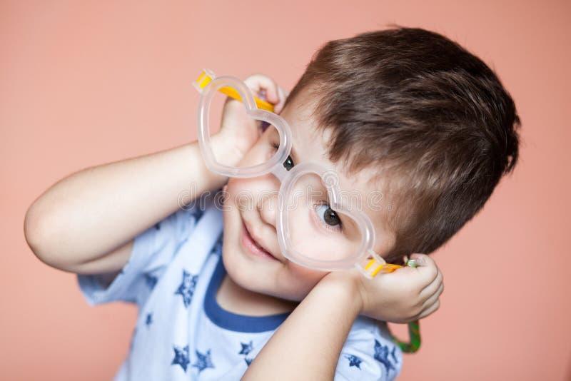 Portrait of cute little boy wearing heart shaped glasses stock image