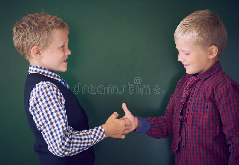 Portrait of cute little boys playing and fool around in classroom during the break between lessons. Portrait of cute little boys playing and fool around in royalty free stock images