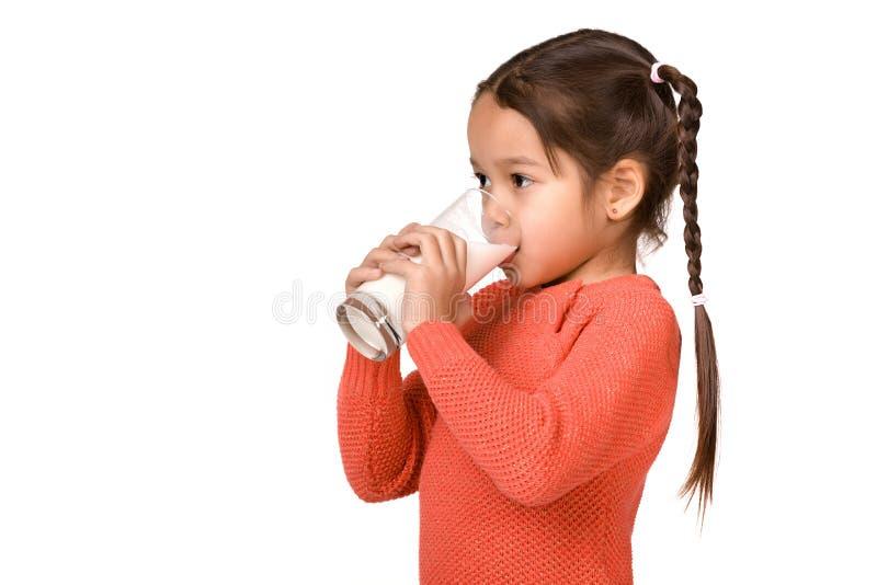 Little child girl holding glass of milk on white background. Portrait of cute little child girl drinking fresh milk isolated on white stock image