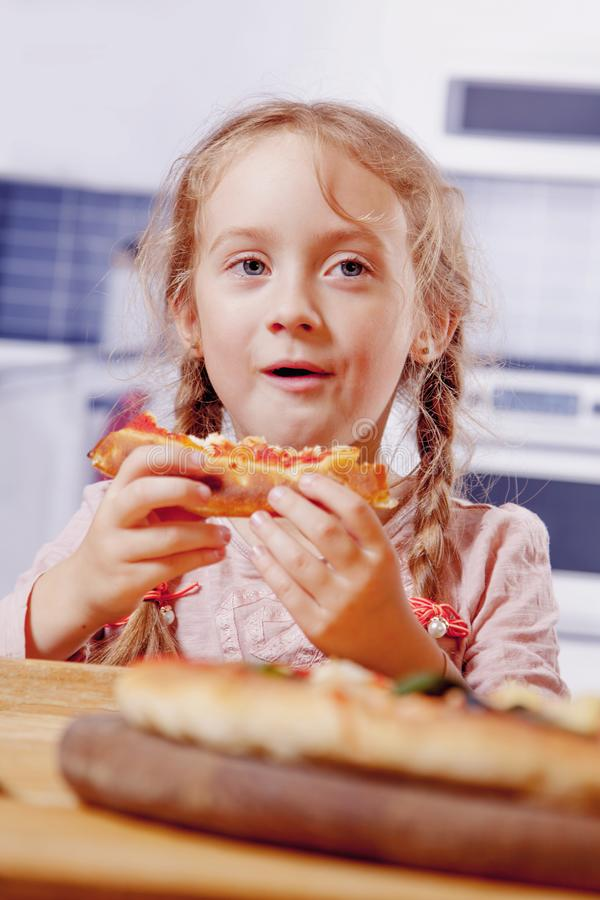 Portrait of cute little child girl eating pizza snack indoors royalty free stock photography
