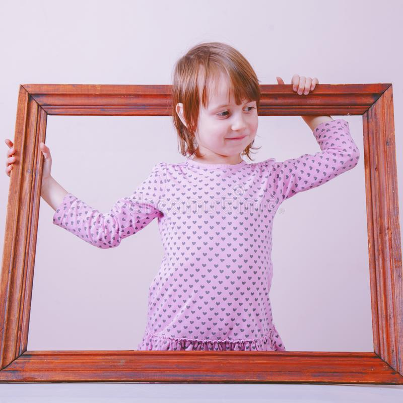 Portrait of cute little child girl extending rules beyond the frame. Freedom and development concept stock photo