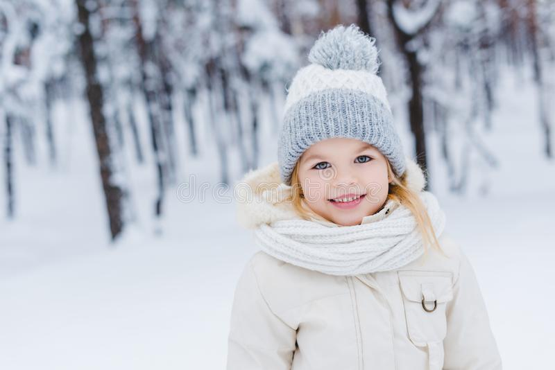 Portrait of cute little child in hat and scarf smiling at camera. In winter park royalty free stock photos