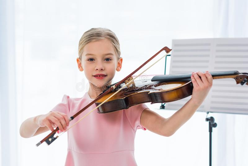 Portrait of cute little child in pink dress playing violin. At home royalty free stock images
