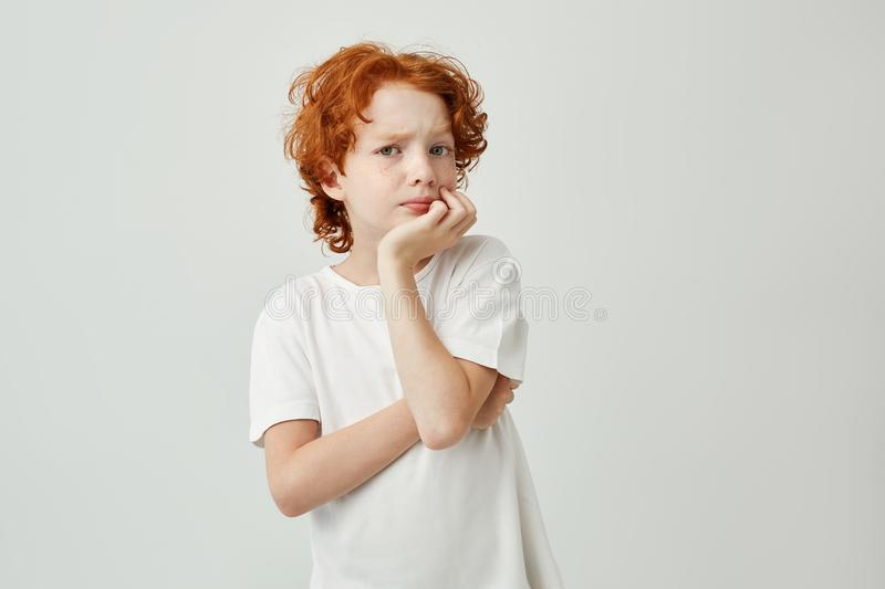Portrait of cute little child with red hair and freckles holding head with hand thinking about homework he need to do. Till evening royalty free stock image
