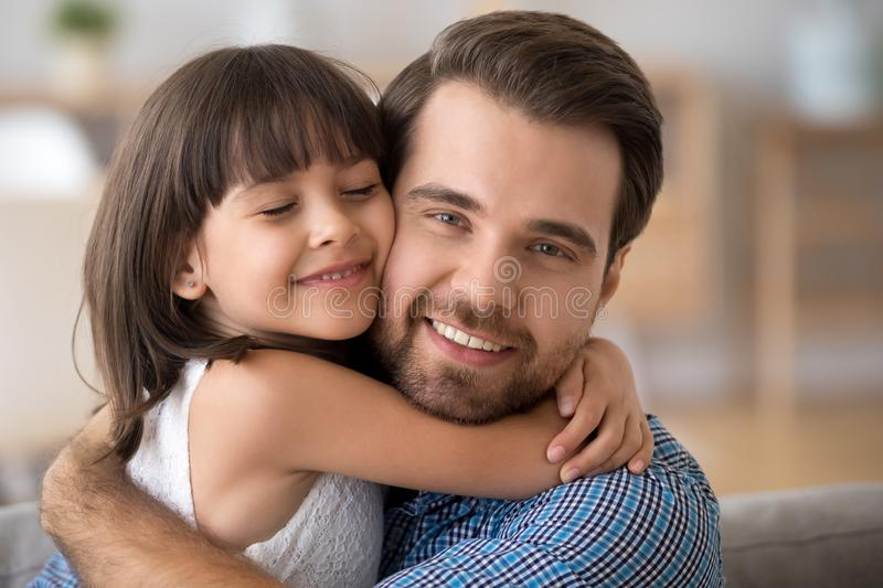 Portrait of cute little daughter hug young father stock photos