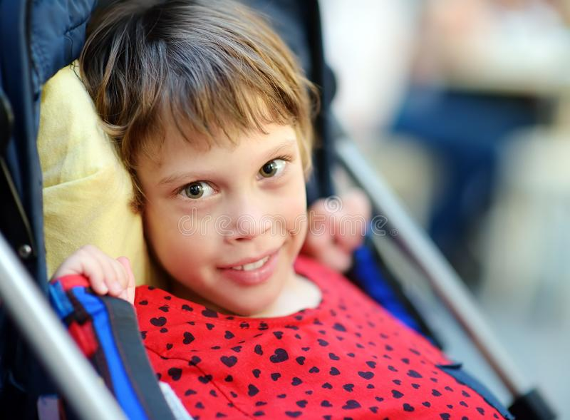 Portrait of a cute little disabled girl in a wheelchair. Child cerebral palsy. Inclusion. Family with disabled kid stock photography