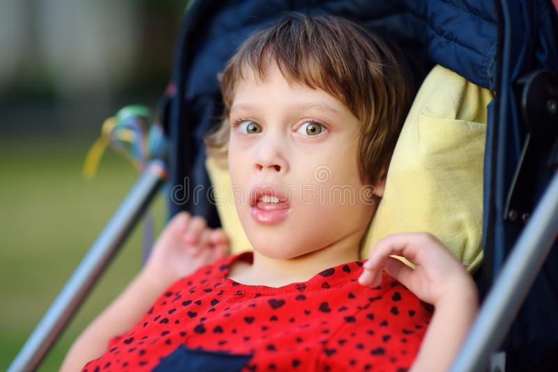 Portrait of a cute little disabled girl in a wheelchair. Child cerebral palsy. Inclusion. Family with disabled kid royalty free stock photo