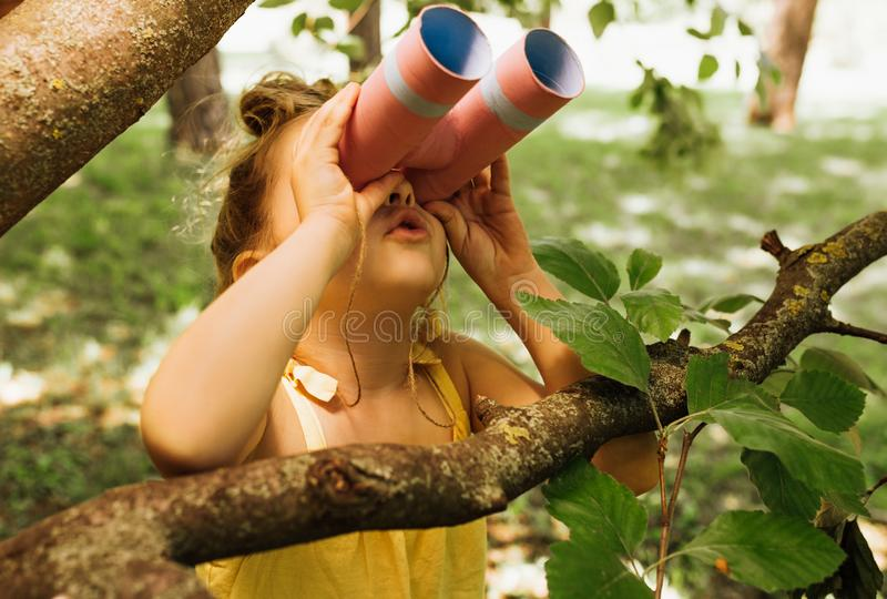 Portrait of cute little explorer girl looking through a binoculars exploring and learning the nature life in summer day in park. Happy child playing pretend stock photography