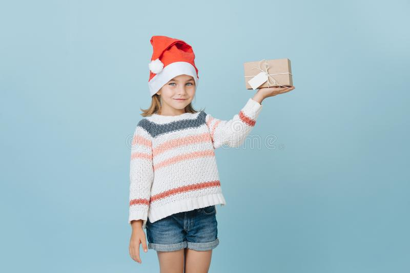 Portrait of cute little first grader girl in a santa`s hat holding present stock image
