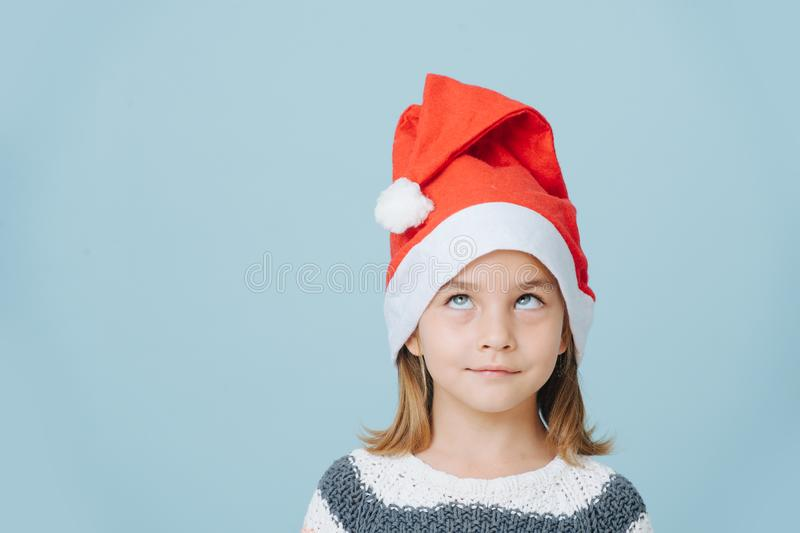 Portrait of cute little first grader girl in a santa`s hat and knitted sweater royalty free stock photos