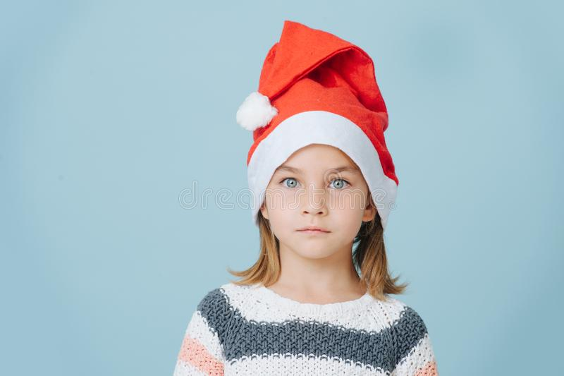 Portrait of cute little first grader girl in a santa`s hat and knitted sweater. royalty free stock image