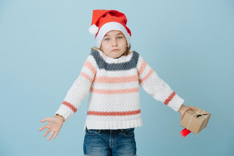 Portrait of cute little first grader girl in a santa`s hat shrugging shoulders royalty free stock images