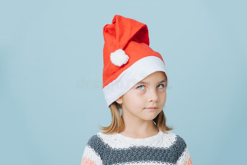 Portrait of cute little first grader girl in a santa`s hat and knitted sweater stock image