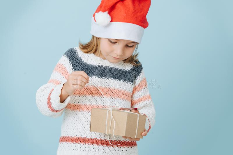 Portrait of cute little first grader girl in a santa`s hat opening present royalty free stock photography