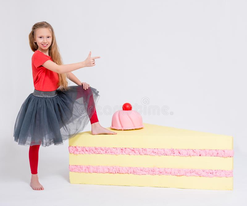 Portrait of cute little girl with big slice of cake pointing at something on copy space over white stock photography