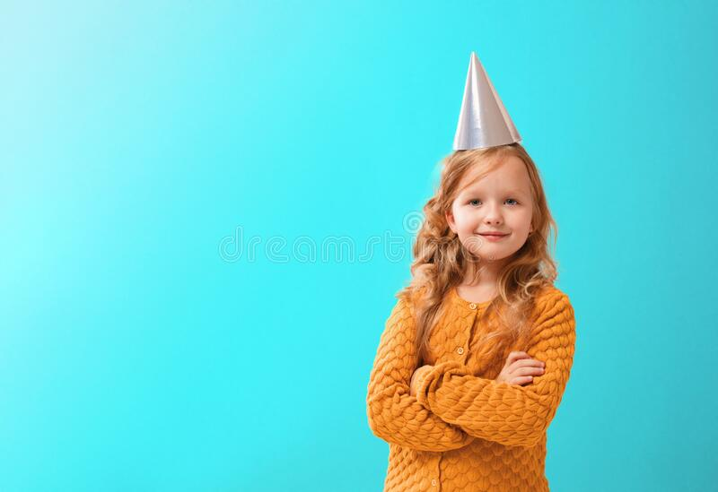 Portrait of a cute little girl in a birthday hat on a turquoise background. Child waiting for celebration royalty free stock images