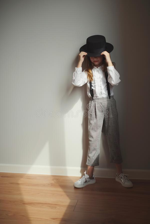Cute little girl with black hat at home stock photography