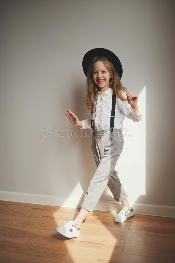 Cute little girl with black hat at home stock photos