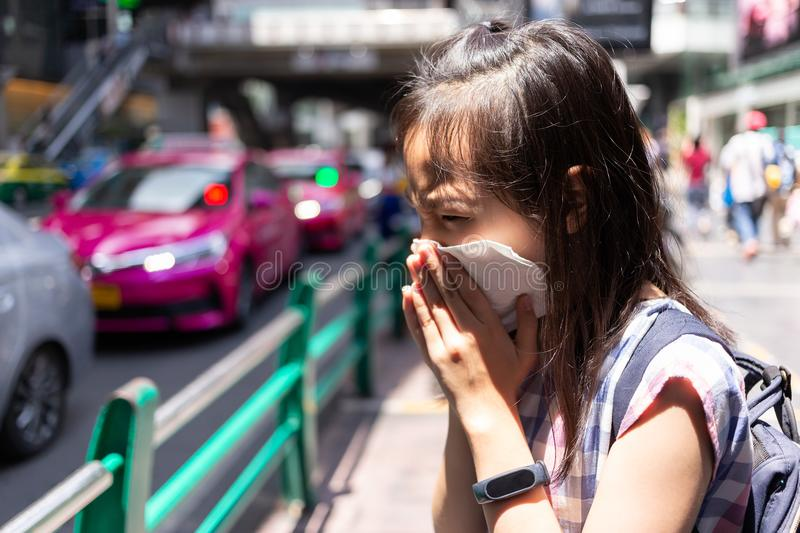 portrait of cute little girl blowing nose in paper handkerchief,Asian girl sneezing in a tissue in the city street concept of pol stock photo