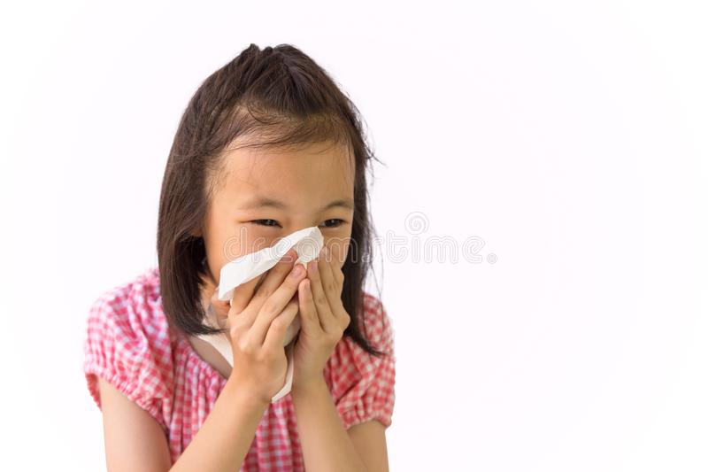 Portrait of cute little girl blowing nose in paper handkerchief,Asian girl sneezing in a tissue isolated on white background,hay stock image