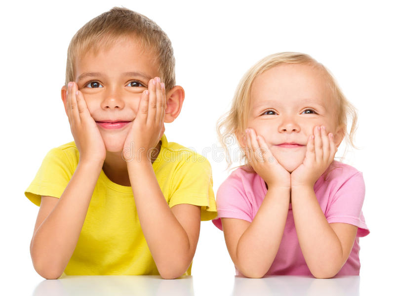 Portrait of a cute little girl and boy. Supporting their heads with hands, isolated over white royalty free stock photography