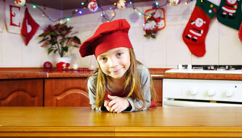 Portrait of cute little girl chef in the christmas kitchen stock photo