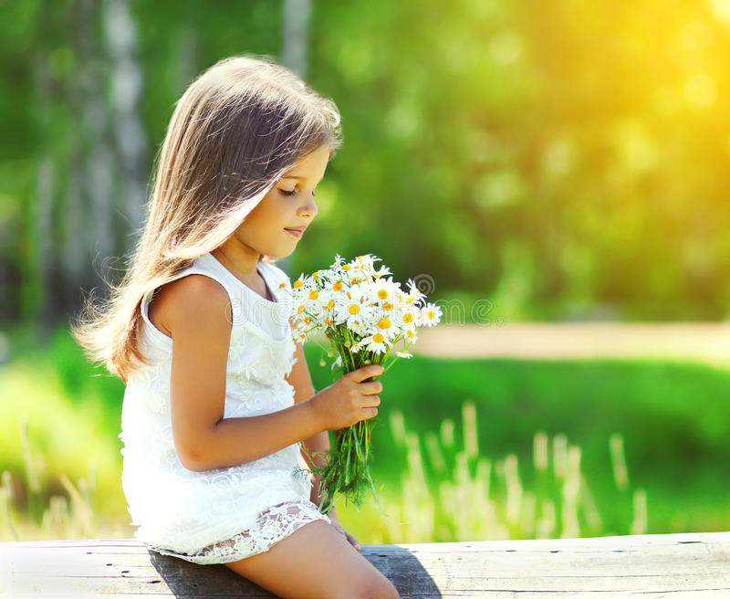 Portrait of cute little girl child with bouquet flowers. Portrait of cute little girl child with bouquet of chamomiles flowers in sunny summer day stock image