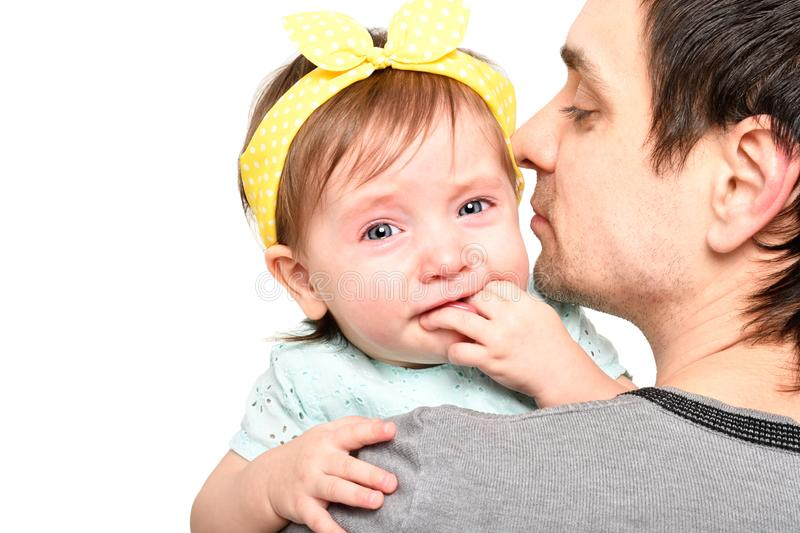 Portrait of a cute little girl crying on the hands of her father royalty free stock image