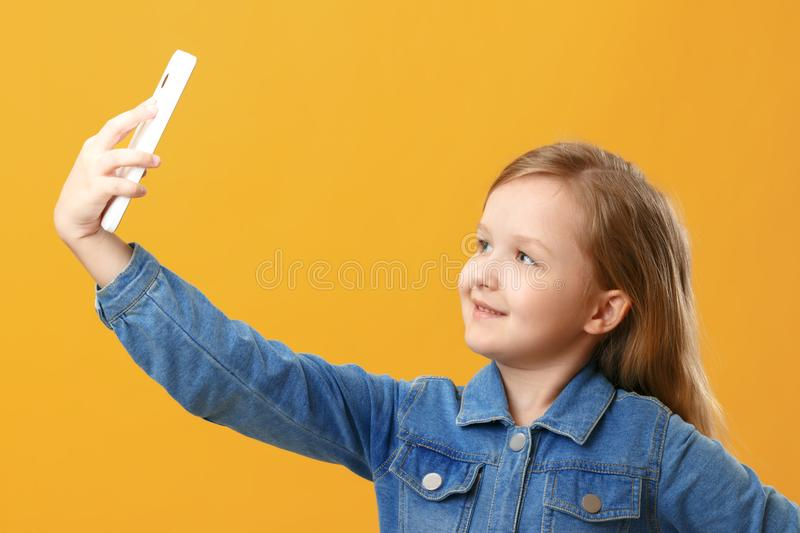 Portrait of a cute little girl in a denim shirt on a yellow background. The child holds the phone and takes a selfie royalty free stock photo
