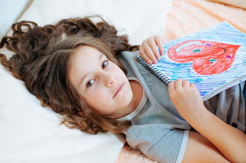 Portrait of cute little girl drawing pictures sitting on bed in cozy childrens room stock image