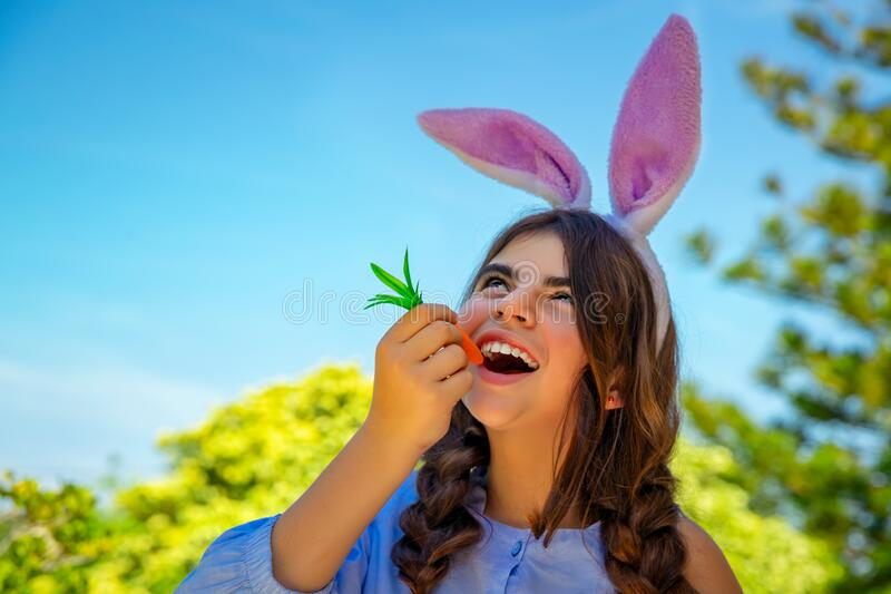 Easter bunny eating carrots. Portrait of a cute little girl dressed as bunny with pleasure eating carrot, traditional Easter symbol, happy spring time outdoors stock photography