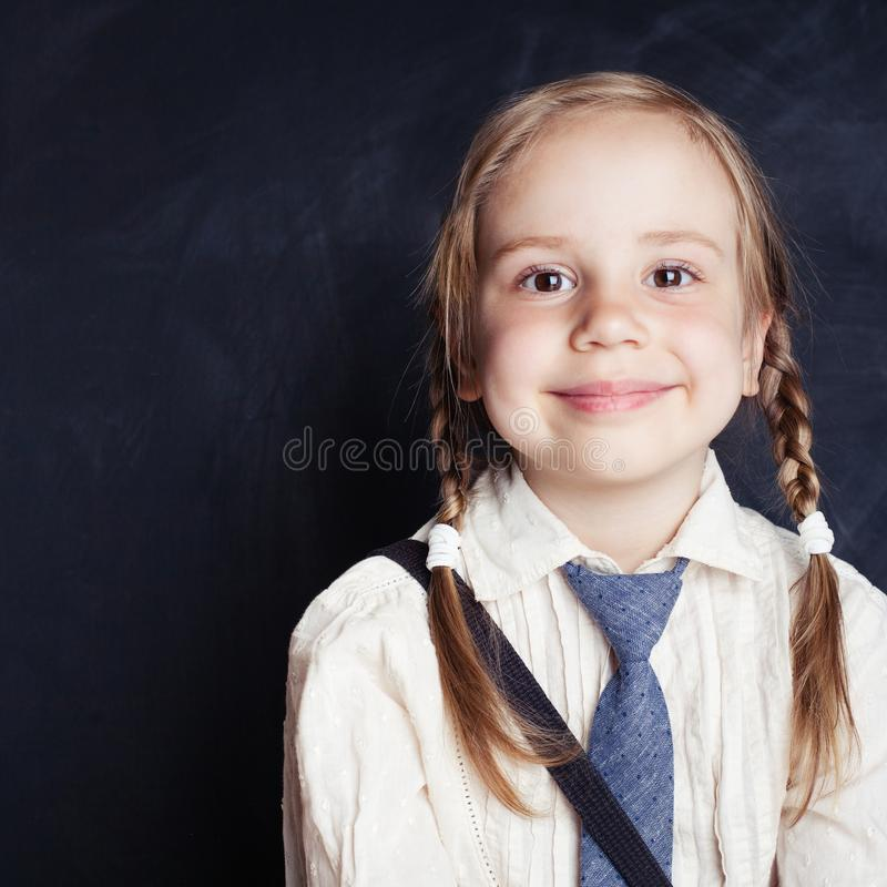 Portrait of cute little girl. Happy child smiling on empty black. Board background with copy space. Back to school royalty free stock photo