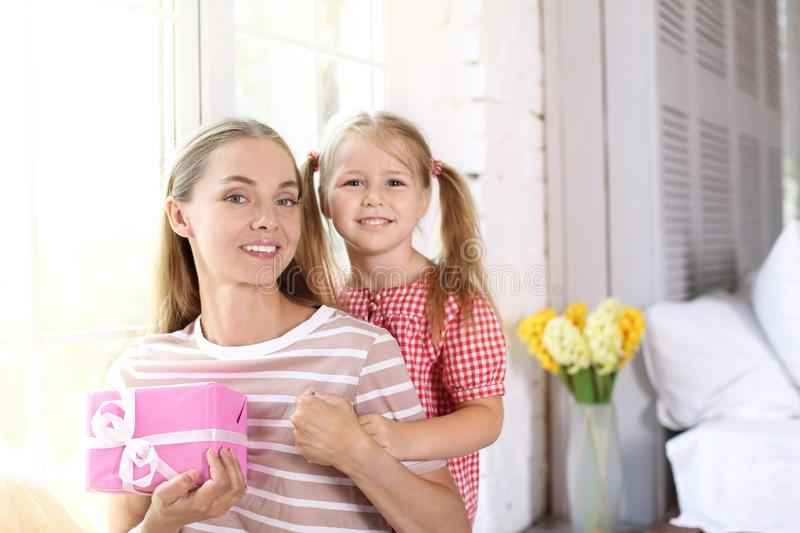 Portrait of cute little girl and her mother with gift box at home stock photo