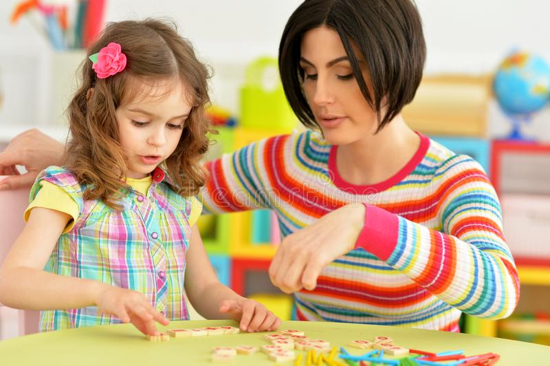 Portrait of cute little girl with her mother studying. Cute little girl with her mother studying royalty free stock image