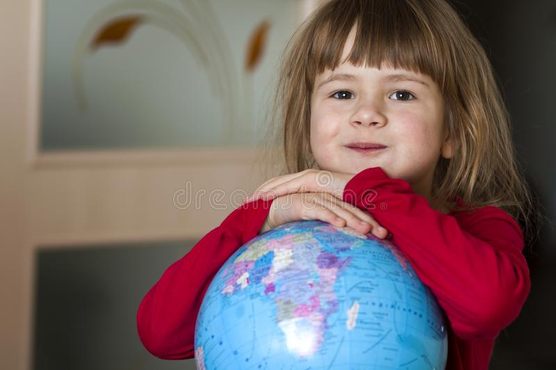 Portrait of the cute little girl hugging the earth globe. Education and save the earth concept. Pretty child looking in the camera royalty free stock image