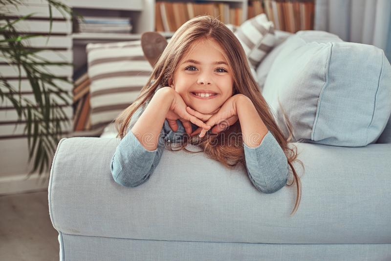 Portrait of a cute little girl with long brown hair, piercing glance and charming smile, looking at a camera, lying on a royalty free stock photography