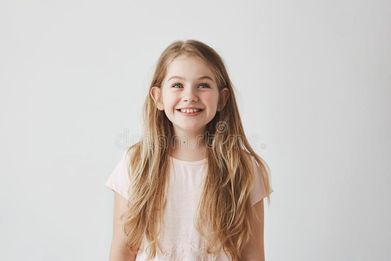 Portrait of cute little girl with long light hair smiling brightfully, looking upside on colorful flying balloons with royalty free stock photo