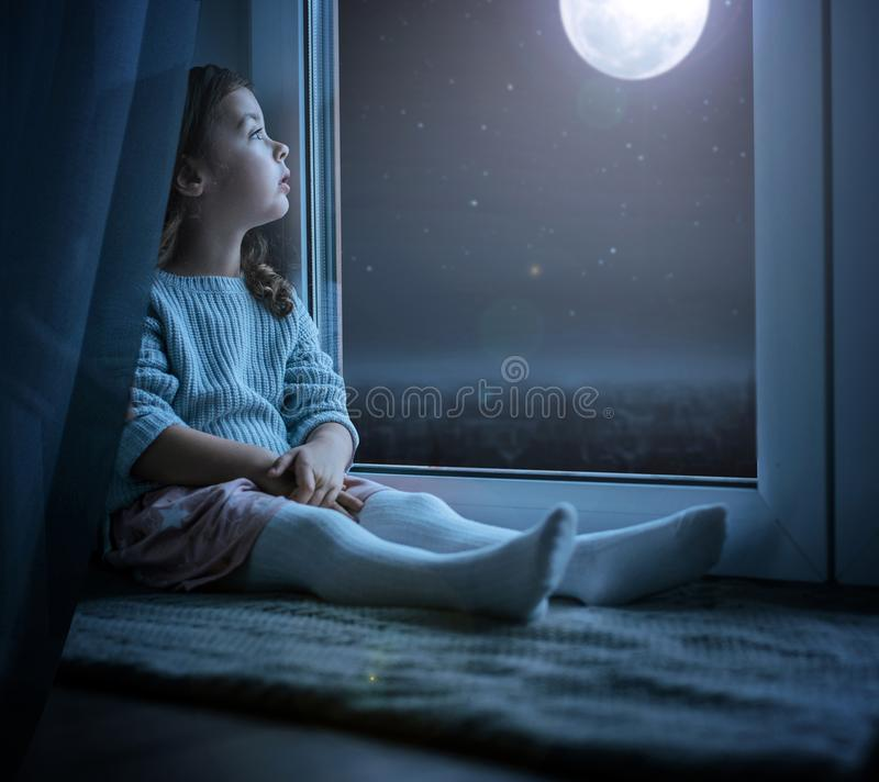 Portrait of a cute little girl looking at the night moon. Portrait of a cute little kidl looking at the night moon stock images