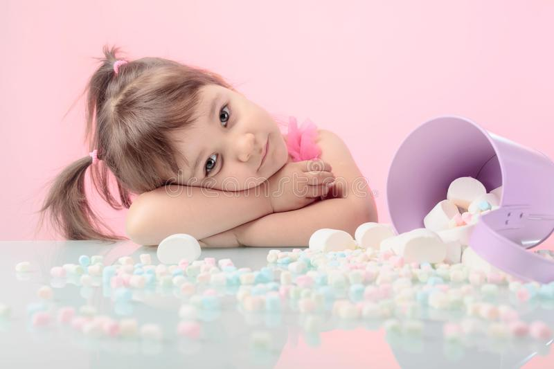 Portrait of a cute little girl with marshmallow on pink backgrou royalty free stock photo