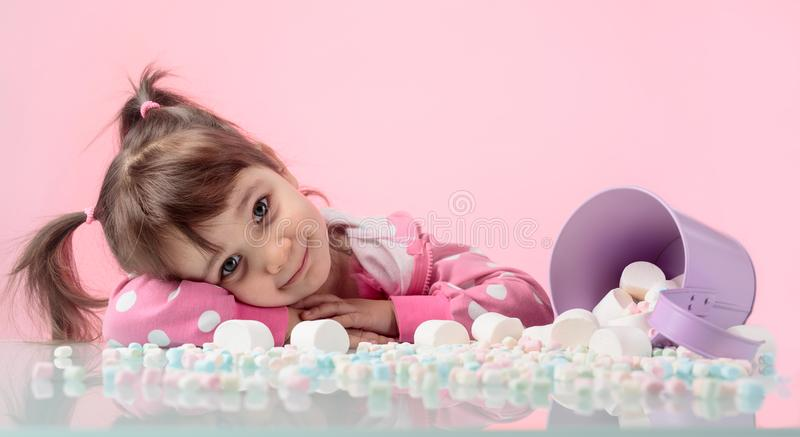 Portrait of a cute little girl with marshmallow on pink background. stock photography