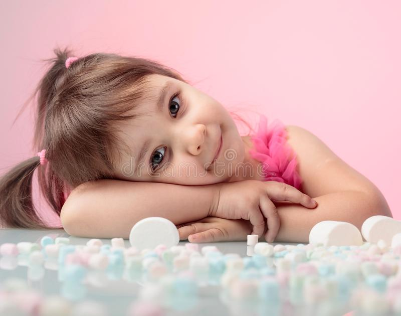 Portrait of a cute little girl with marshmallow on pink background. stock photo